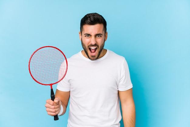 Jonge knappe man spelen badminton geïsoleerd schreeuwen erg boos en agressief.