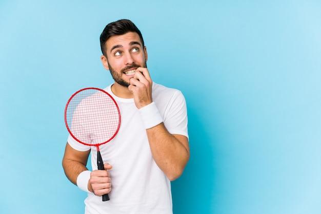 Jonge knappe man spelen badminton ontspannen denken over iets kijken naar een lege ruimte.