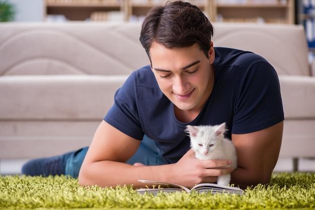 Jonge knappe man spelen met witte kitten