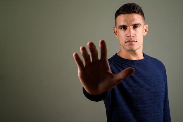 Jonge knappe man stopbord gebaar maken tegen gekleurde achtergrond