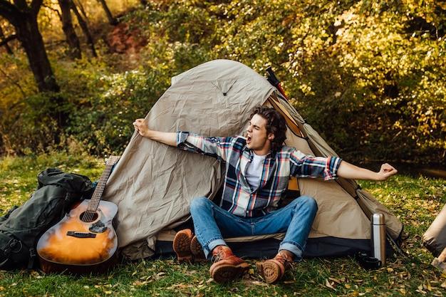 Jonge knappe man strekt zich uit in de ochtend in de buurt van de tent op de camping in de natuur