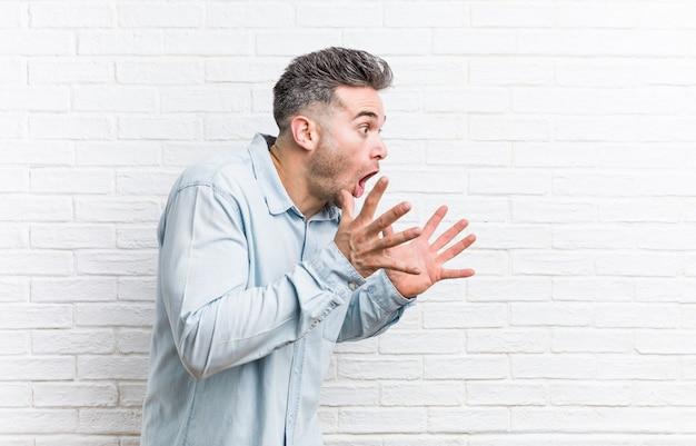 Jonge knappe man tegen bakstenen muur schreeuwt luid, houdt ogen open en handen gespannen