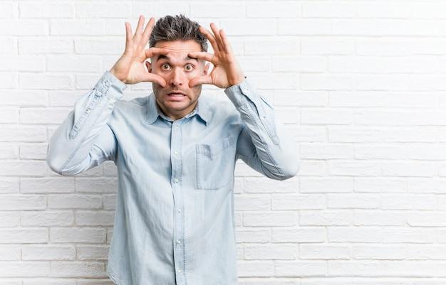 Jonge knappe man tegen een bakstenen muur die ogen geopend houdt om een succeskans te vinden.