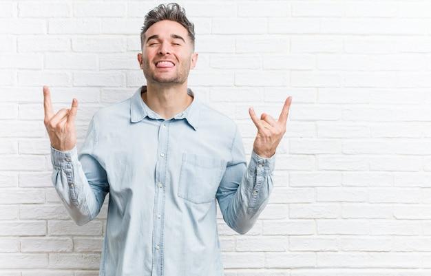 Jonge knappe man tegen een bakstenen muur die rotsgebaar met vingers toont