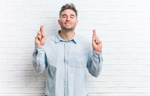 Jonge knappe man tegen een bakstenen muur die vingers kruist voor het hebben van geluk
