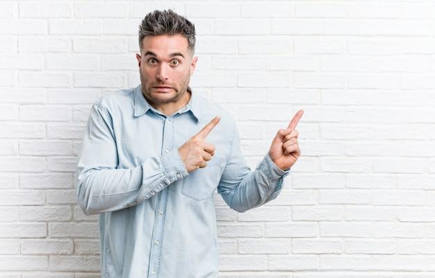 Jonge knappe man tegen een bakstenen muur geschokt wijzend met wijsvingers naar een kopie ruimte.