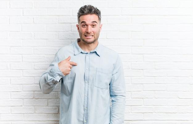 Jonge knappe man tegen een bakstenen muur persoon wijst met de hand naar een shirt kopie ruimte, trots en zelfverzekerd