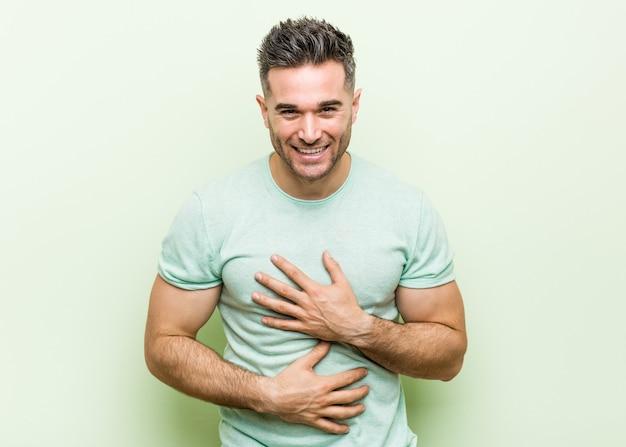 Jonge knappe man tegen een groene achtergrond lacht vrolijk en heeft plezier met het houden van handen op de buik.