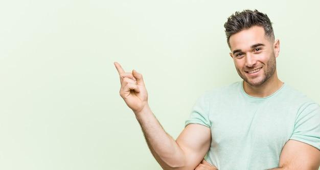Jonge knappe man tegen een groene glimlach vrolijk wijzend met wijsvinger weg.