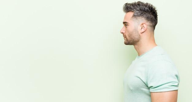 Jonge knappe man tegen een groene starende linkerzijde, zijwaarts poseren.