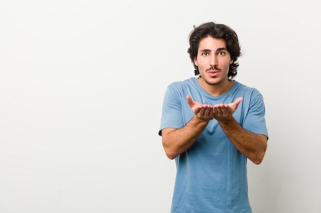 Jonge knappe man tegen een witte achtergrond die lippen vouwt en palmen houdt om luchtkus te verzenden.