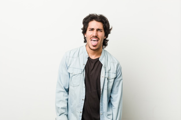 Jonge knappe man tegen een witte achtergrond grappige en vriendelijke tong uitsteekt.