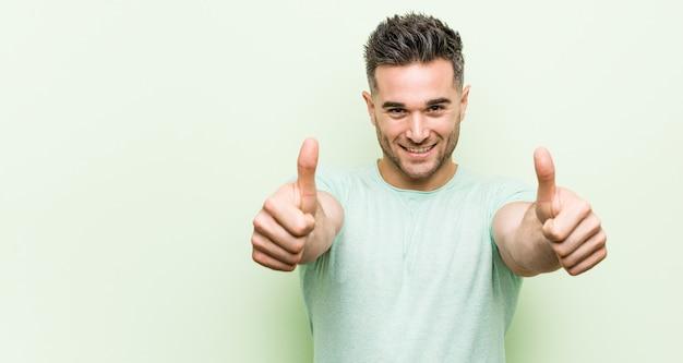 Jonge knappe man tegen groen met duim omhoog, proost over iets, steun en respect.