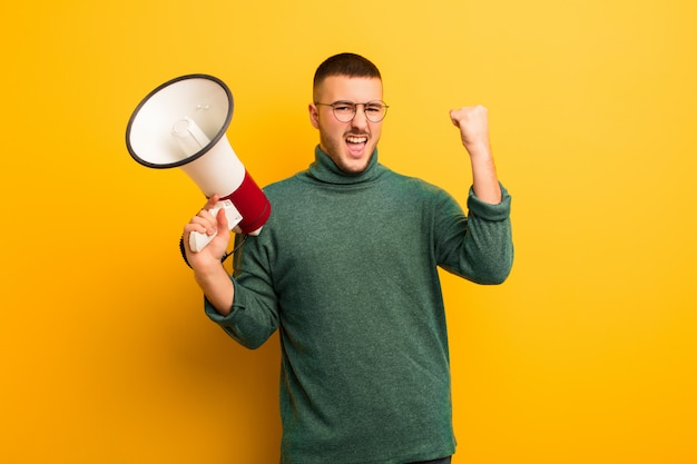 Jonge knappe man tegen platte muur met een megafoon