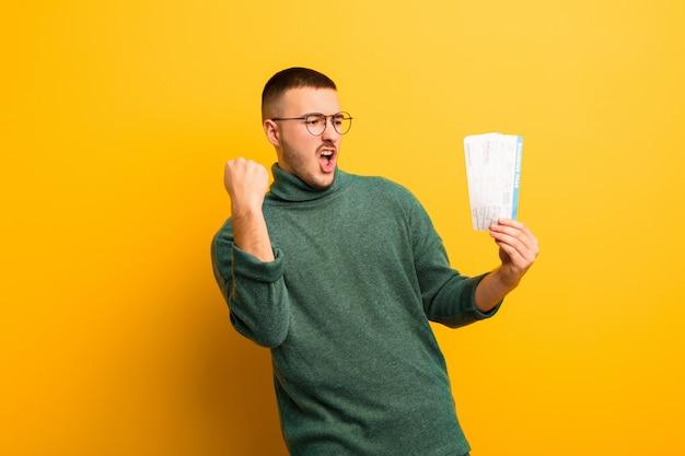 Jonge knappe man tegen platte muur met instapkaartkaartjes