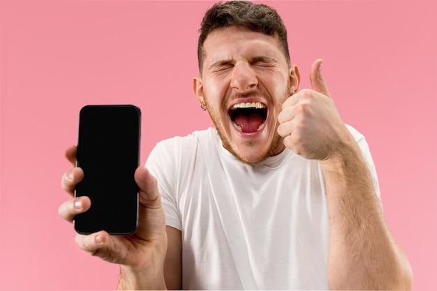 Jonge knappe man toont smartphonescherm geïsoleerd op roze achtergrond in shock met een verrassing