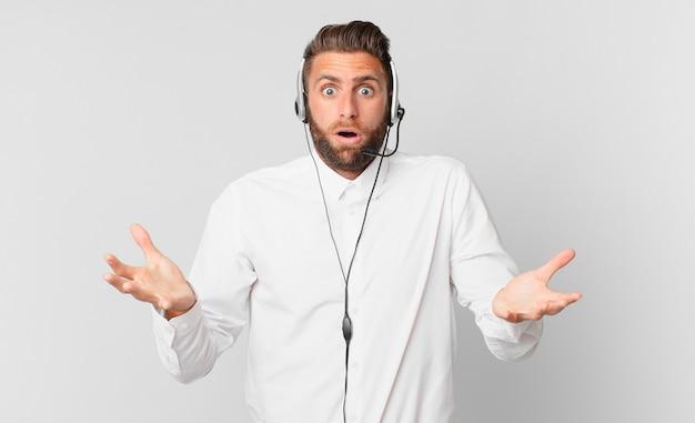Jonge knappe man verbaasd, geschokt en verbaasd met een ongelooflijke verrassing. telemarketing concept