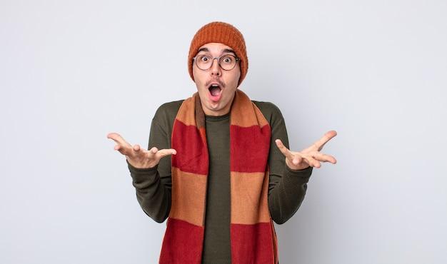 Jonge knappe man verbaasd, geschokt en verbaasd met een ongelooflijke verrassing. winterkleren concept