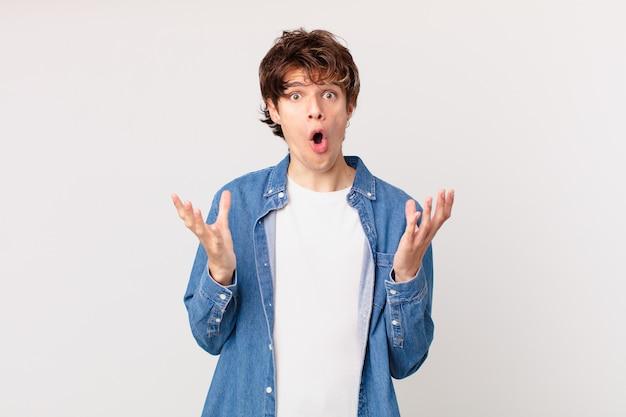 Jonge knappe man verbaasd, geschokt en verbaasd met een ongelooflijke verrassing