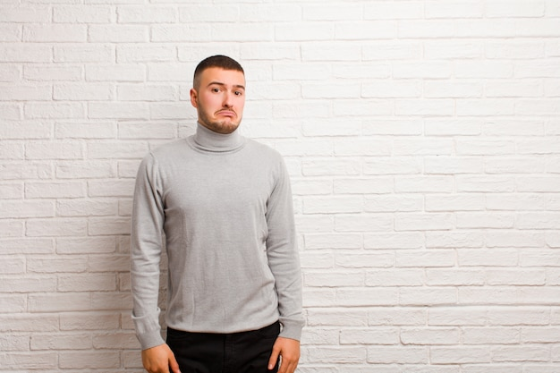 Jonge knappe man verdrietig en gestrest, boos vanwege een onaangename verrassing, met een negatieve, angstige blik tegen de vlakke muur