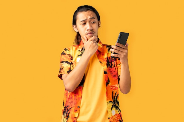 Jonge knappe man verward met de smartphone in de hand
