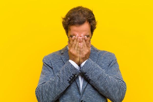 Jonge knappe man voelt verdrietig, gefrustreerd, nerveus en depressief, bedekkend gezicht met beide handen, huilende oranje muur