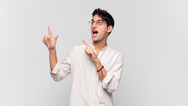Jonge knappe man voelt zich blij en verrast, lacht met een geschokte uitdrukking en wijst naar de zijkant