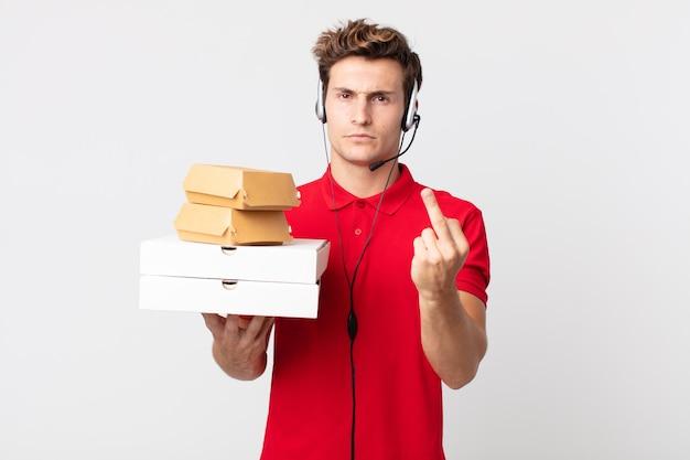 Jonge knappe man voelt zich boos, geïrriteerd, opstandig en agressief. afhaal fastfood concept