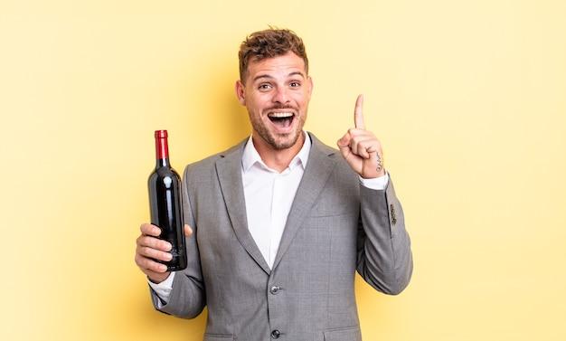 Jonge knappe man voelt zich een gelukkig en opgewonden genie nadat hij een idee heeft gerealiseerd. fles wijn concept