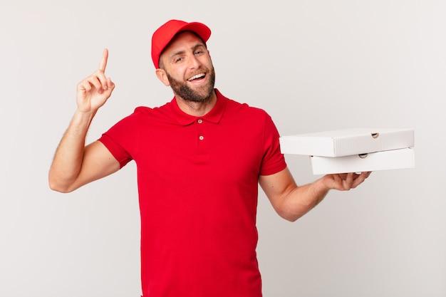 Jonge knappe man voelt zich een gelukkig en opgewonden genie nadat hij een idee heeft gerealiseerd. pizza bezorgconcept