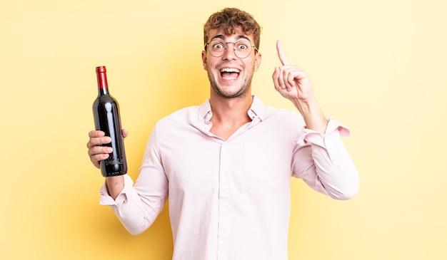 Jonge knappe man voelt zich een gelukkig en opgewonden genie nadat hij een idee heeft gerealiseerd. wijnfles concept