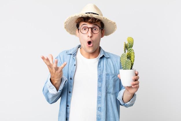 Jonge knappe man voelt zich extreem geschokt en verrast. boer met een decoratieve cactus