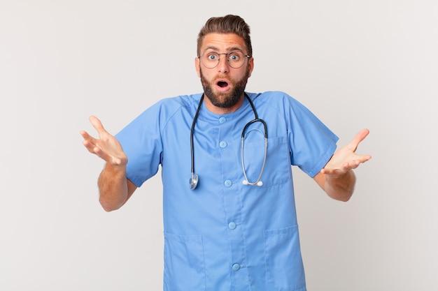 Jonge knappe man voelt zich extreem geschokt en verrast. verpleegster concept