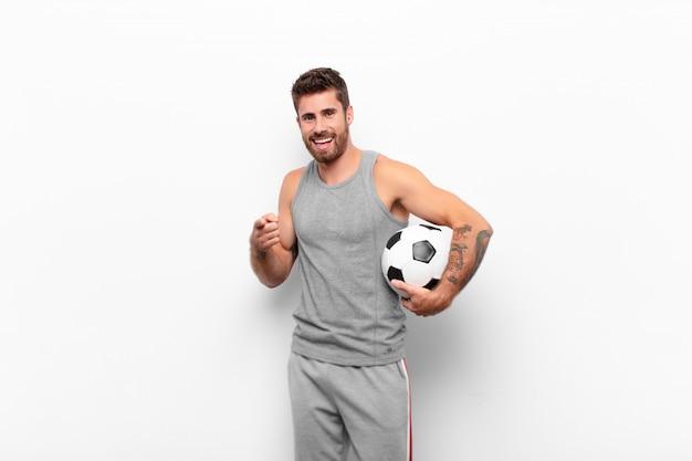 Jonge knappe man voelt zich gelukkig, cool, tevreden, ontspannen en succesvol, wijzend op de camera, kiest u met een voetbal