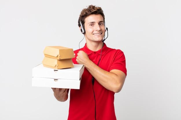 Jonge knappe man voelt zich gelukkig en staat voor een uitdaging of feest. afhaal fastfood concept