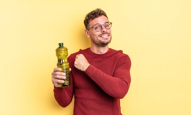 Jonge knappe man voelt zich gelukkig en staat voor een uitdaging of feest. olijfolie concept