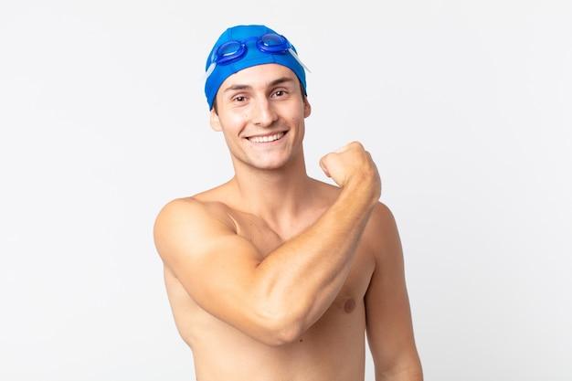 Jonge knappe man voelt zich gelukkig en staat voor een uitdaging of feest. zwemmer concept