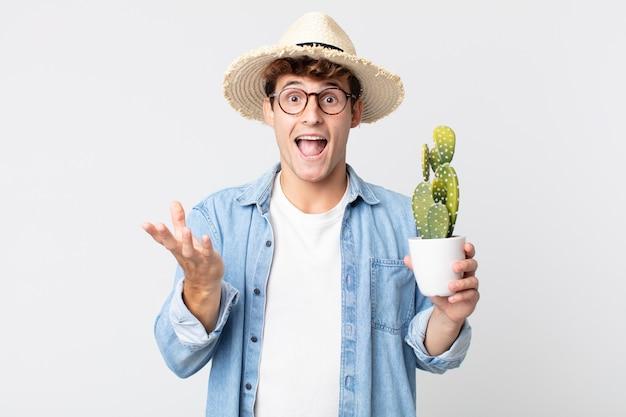 Jonge knappe man voelt zich gelukkig en verbaasd over iets ongelooflijks. boer met een decoratieve cactus