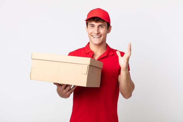 Jonge knappe man voelt zich gelukkig en verbaasd over iets ongelooflijks leveringspakket serviceconcept.