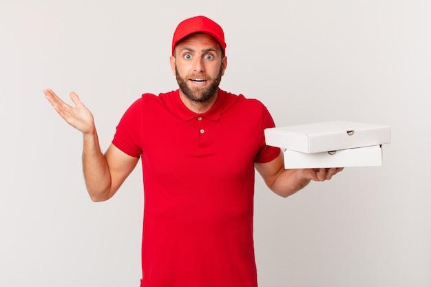 Jonge knappe man voelt zich gelukkig en verbaasd over iets ongelooflijks. pizza bezorgconcept