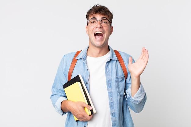 Jonge knappe man voelt zich gelukkig en verbaasd over iets ongelooflijks. universitair studentenconcept