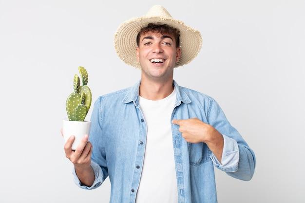 Jonge knappe man voelt zich gelukkig en wijst naar zichzelf met een opgewonden boer met een decoratieve cactus