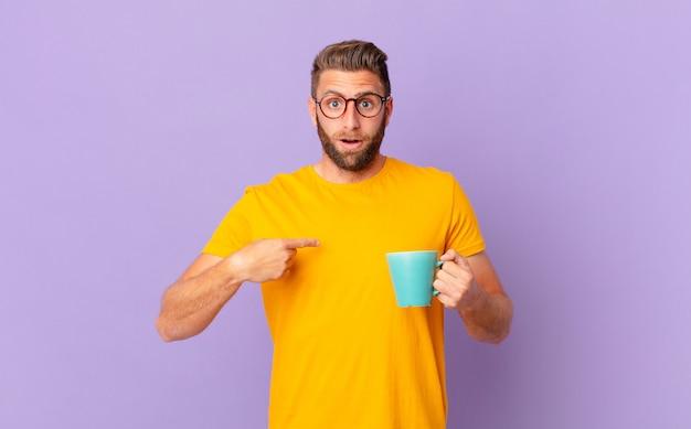 Jonge knappe man voelt zich gelukkig en wijst naar zichzelf met een opgewonden en een koffiemok vasthouden