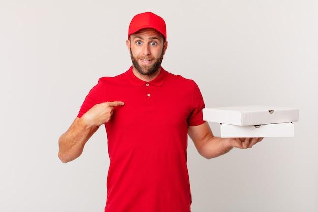 Jonge knappe man voelt zich gelukkig en wijst naar zichzelf met een opgewonden pizza bezorgconcept