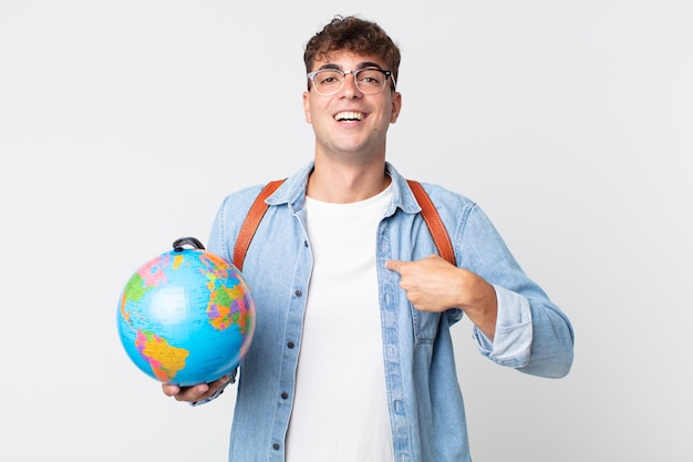 Jonge knappe man voelt zich gelukkig en wijst naar zichzelf met een opgewonden student met een wereldbolkaart