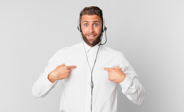 Jonge knappe man voelt zich gelukkig en wijst naar zichzelf met een opgewonden telemarketing concept