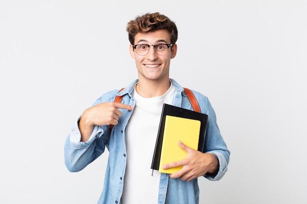 Jonge knappe man voelt zich gelukkig en wijst naar zichzelf met een opgewonden universitair studentenconcept