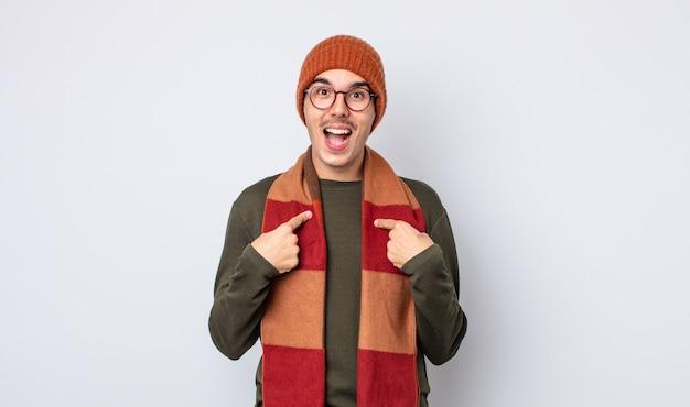 Jonge knappe man voelt zich gelukkig en wijst naar zichzelf met een opgewonden winterkleren concept