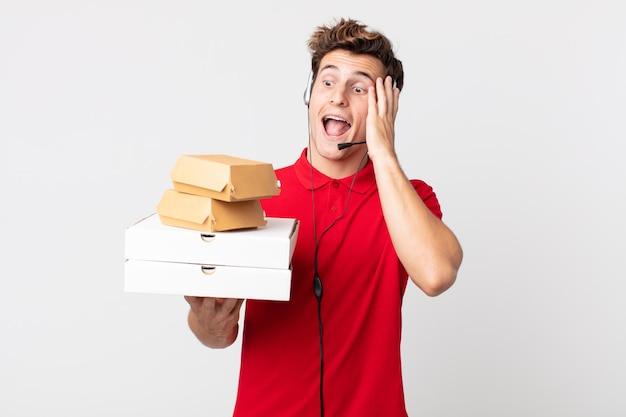 Jonge knappe man voelt zich gelukkig, opgewonden en verrast. afhaal fastfood concept