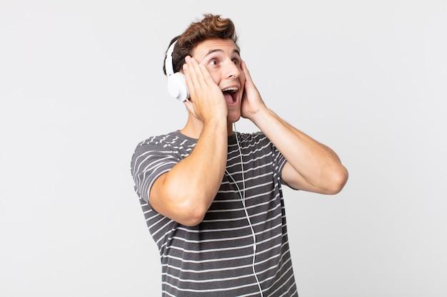 Jonge knappe man voelt zich gelukkig, opgewonden en verrast. luisteren muziek concept